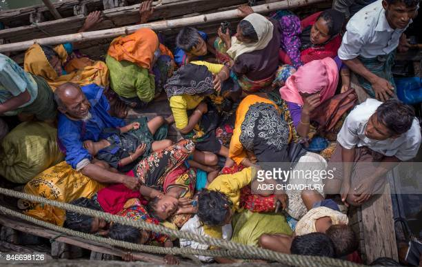 TOPSHOT This photograph taken on September 12 2017 shows Rohingya refugees arriving by boat at Shah Parir Dwip on the Bangladesh side of the Naf...
