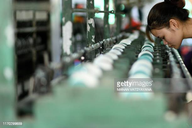 This photograph taken on September 17, 2019 shows a worker checking finished silk thread bobbins at a workshop in Co Chat village in Vietnam's Nam...