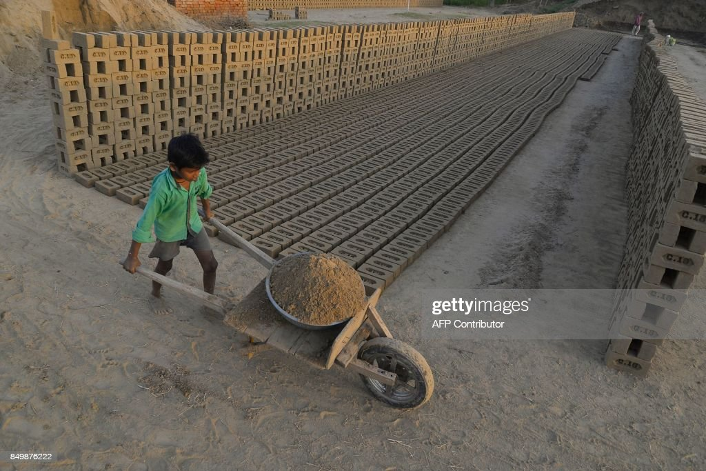 This photograph taken on September 18 2017 shows an Indian boy working at a brick kiln on the outskirts of Jalandhar Brick kiln workers in India are..