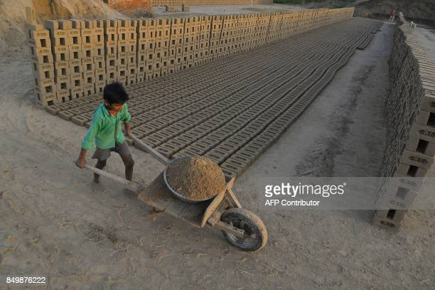 This photograph taken on September 18 2017 shows an Indian boy working at a brick kiln on the outskirts of Jalandhar Brick kiln workers in India are...