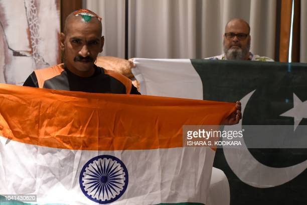 This photograph taken on September 19 2018 shows Indian cricket fan Sudhir Kumar and Pakistan cricket fan Mohammad Basheer holding their respective...