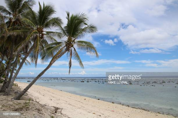This photograph taken on September 2 2018 shows a beach view in Ewa on the Pacific island of Nauru A cluster of corrugated iron huts resembling...