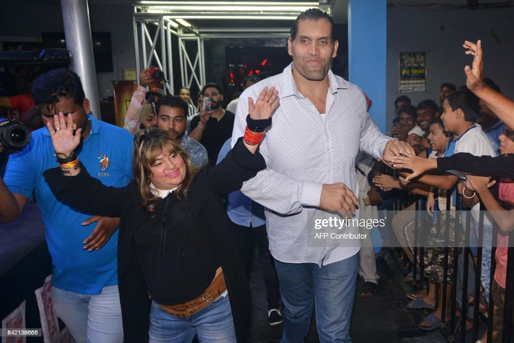 This photograph taken on September 2 shows Indianborn US professional wrestler Dalip Singh Rana along with bollywood actress Dolly Bindra gesture to..