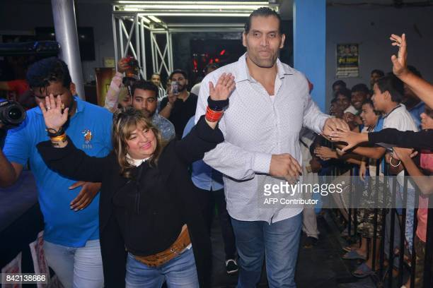This photograph taken on September 2 shows Indianborn US professional wrestler Dalip Singh Rana along with bollywood actress Dolly Bindra gesture to...