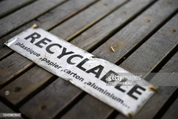 """This photograph taken on September 21 shows a sign for recycling plastic, paper, cardbox and aluminium in Tremargat, western France. - """"Poor and..."""