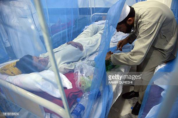 This photograph taken on September 23 2013 shows a Pakistani paramedic staff member treating a patient affected with dengue fever at a hospital in...