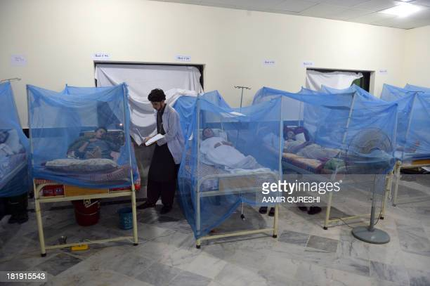 This photograph taken on September 23 2013 shows a Pakistani paramedic staff member checking the report of a dengue fever patient at a hospital in...