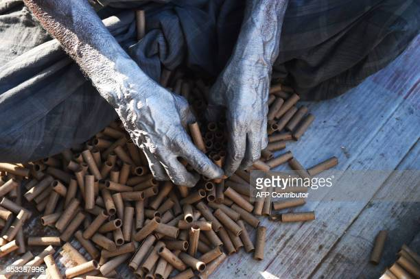 This photograph taken on September 23 2017 shows an Indian worker preparing firecrackers at a workshop on the outskirts of Ahmedabad / AFP PHOTO /...