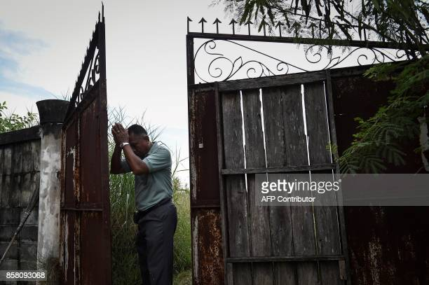 This photograph taken on September 23, 2017 shows Chumpol Thummai praying to the abandoned gate where his left-wing activist brother was lynched by...