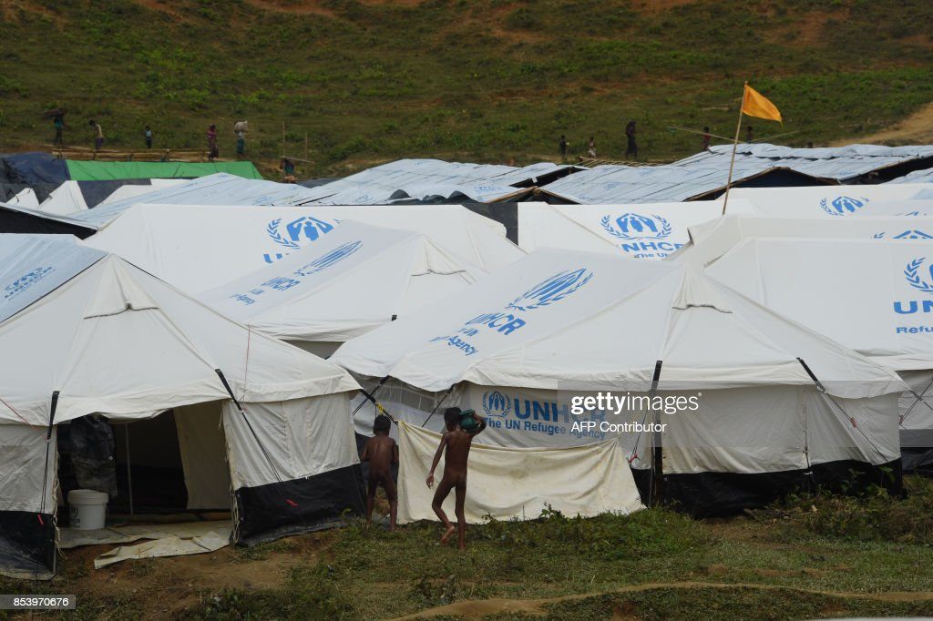 This photograph taken on September 24 2017 show Rohingya refugees walking past UNHCR tents at & This photograph taken on September 24 2017 show Rohingya refugees ...
