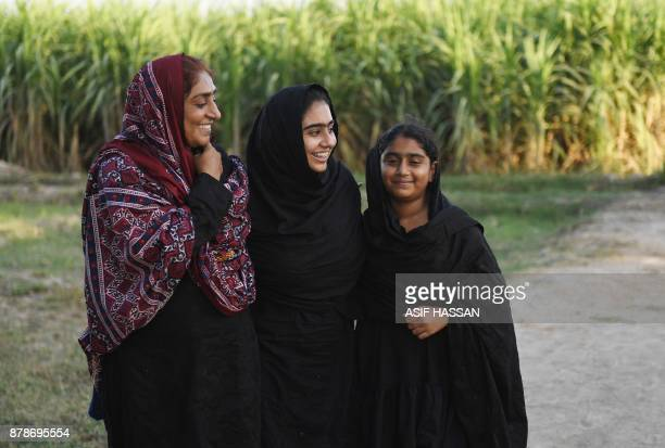 This photograph taken on September 27 2017 shows Pakistani woman Mukhtiar Naz known as Waderi Nazo Dharejo meeting her daughters at her agriculture...