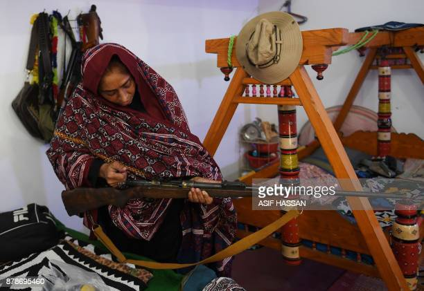 This photograph taken on September 27 shows Pakistani woman Mukhtiar Naz known as Waderi Nazo Dharejo checking a gun at her ancestral home in Qazi...