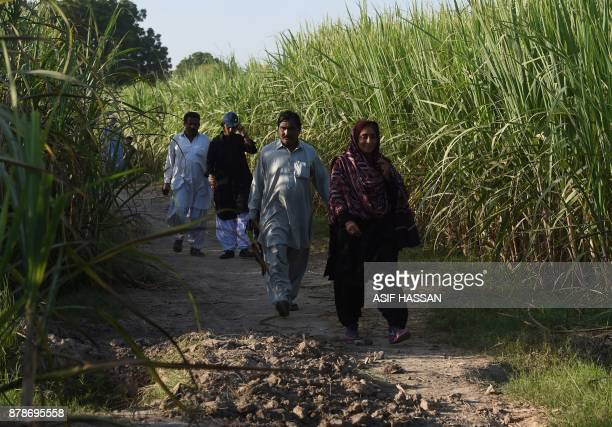 This photograph taken on September 27 shows Pakistani woman Mukhtiar Naz known as Waderi Nazo Dharejo walking with her guard into her agriculture...