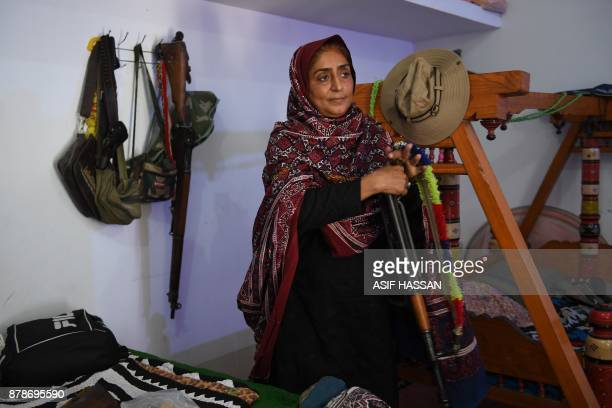 This photograph taken on September 27 shows Pakistani woman Mukhtiar Naz known as Waderi Nazo Dharejo holding a gun at her ancestral home in Qazi...