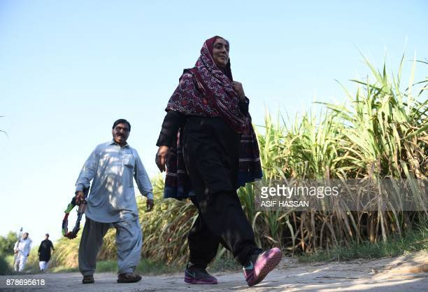 This photograph taken on September 27 shows Pakistani woman Mukhtiar Naz known as Waderi Nazo Dharejo walking her guard at her agriculture field in...