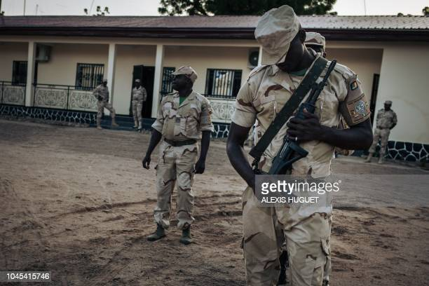 This photograph taken on September 28 shows soldiers as they conduct the daily flaglowering ceremony at the Force Multinationale Mixte Sector No 1...