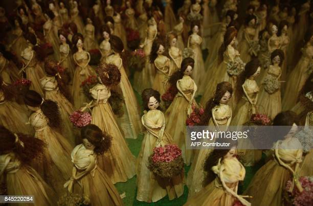 This photograph taken September 9 2017 shows finished dolls made by 35yearold Neli Chachea Mao on display at her workshop in the Indian city of...