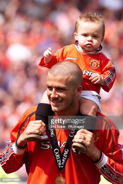 This picture can only be used in the context of an editorial feature Manchester United's David Beckham carries his son Brooklyn on his shoulders as...