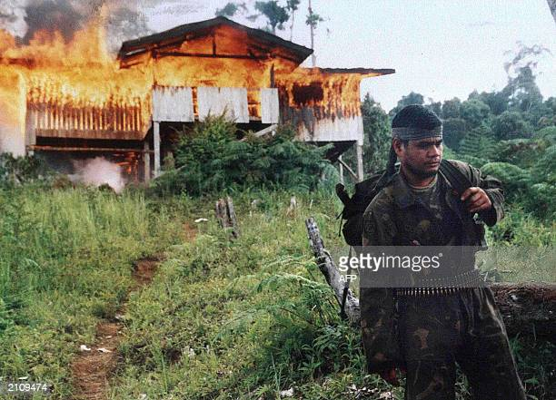 This picture dated 18 June 2003 shows a Philippine Army soldier walking away from a captured burning shelter of Muslim separatist rebels of the Moro...