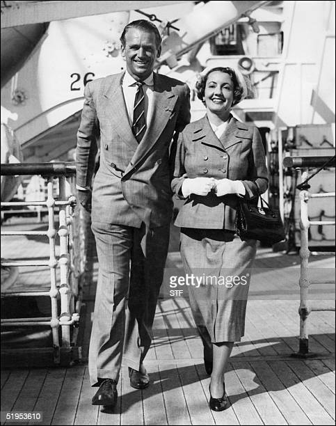 This picture dated 26 August 1948 shows film star Douglas Fairbanks Junior smiling with his wife as he walks the deck of the Queen Elizabeth at...