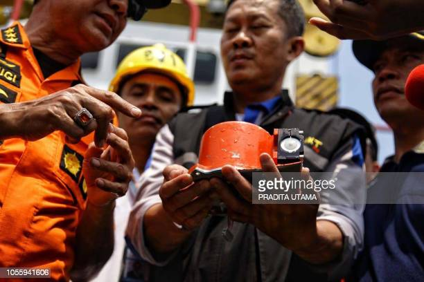 TOPSHOT This picture from Indonesia media agency 'detikcom' shows officials displaying part of the illfated Lion Air flight JT 610's black box an FDR...