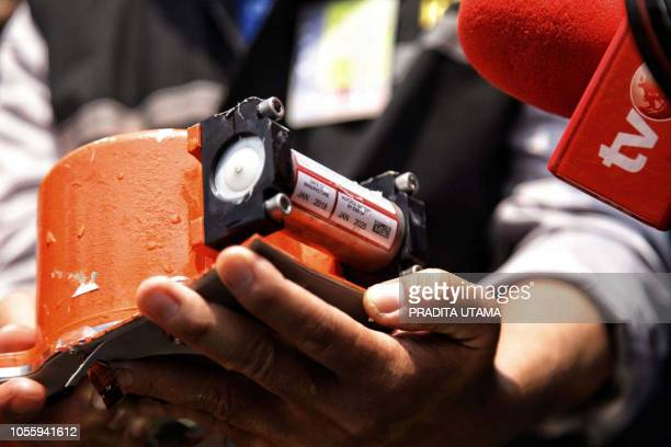 This picture from Indonesia media agency detikcom shows officials displaying part of the illfated Lion Air flight JT 610's black box an FDR after it...