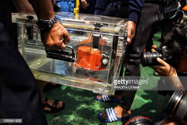 This picture from Indonesia media agency 'detikcom' shows officials displaying part of the illfated Lion Air flight JT 610's black box an FDR after...