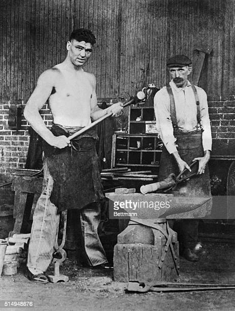 This picture of Jack Dempsey and unidentified friend shows him with a hammer in hand in Chester, PA., shipyard, and attired in overalls helped fan...