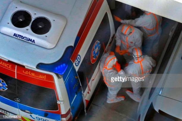 This picture picture taken on February 28 2020 shows an ambulance and an emergency medical response team on the scene at the Crowne Plaza hotel at...