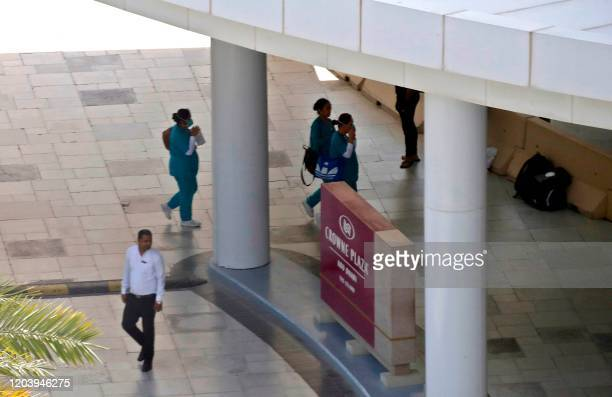 This picture picture taken on February 28 2020 shows healthcare staff walking outside the lobby at the Crowne Plaza hotel at Yas Island Abu Dhabi...