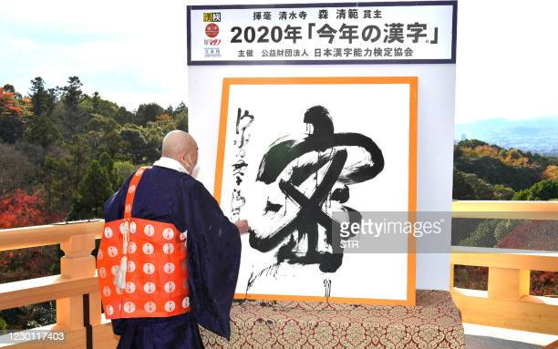 This picture received from Jiji Press shows Seihan Mori, master of the ancient Kiyomizu temple, using calligraphy to write the Chinese character,...