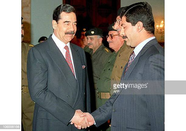 This picture released 08 February by the Iraqi official news agency shows Iraqi President Saddam Hussein greeting his son Qusay who came to visit his...