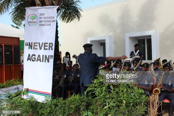 This picture shows a banner reading Never Again is seen as a police band performs during the Truth and Reconciliation and Reparation Commission at...