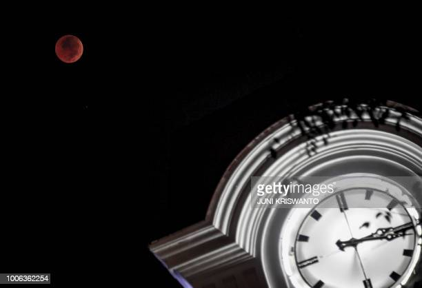 This picture shows a blood moon eclipse as seen from Surabaya in East Java province on July 27 2018 The longest blood moon eclipse this century began...