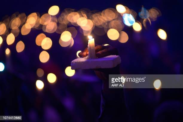 This picture shows a candle hold as Pakistani Christians attend the candle light Carol service during the Christmas celebration in Lahore on December...