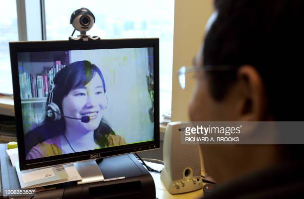 This picture shows a computer user in Hong Kong 27 March 2007 looking at an image of online Mandarin teacher Lily Huang at her home on Hainan island...