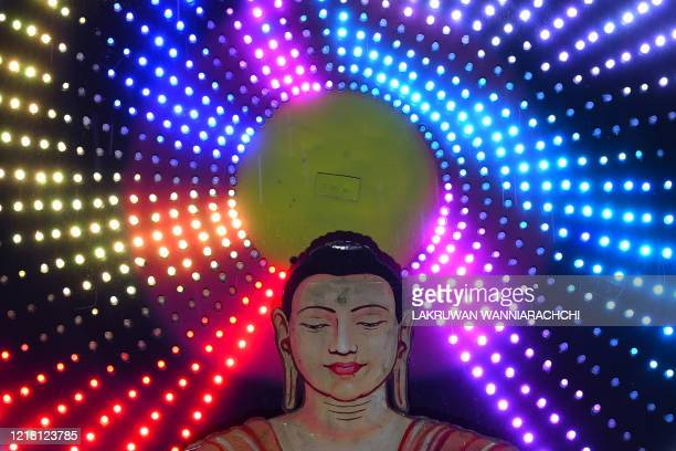 This picture shows a display featuring a seated Buddha during Poson Poya festival in Colombo on June 7 2020 Poson Poya is an annual Buddhist festival...