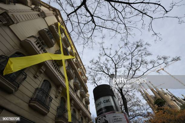 This picture shows a giant yellow ribbon hanging from the facade of a building in front of the Sagrada Famila Basilica in Barcelona on January 3 2018...