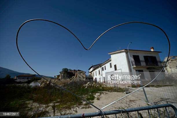 This picture shows a heart sculpted in metal wire in front of damaged buildings following the 2009 earthquake on October 22, 2012 in the village of...