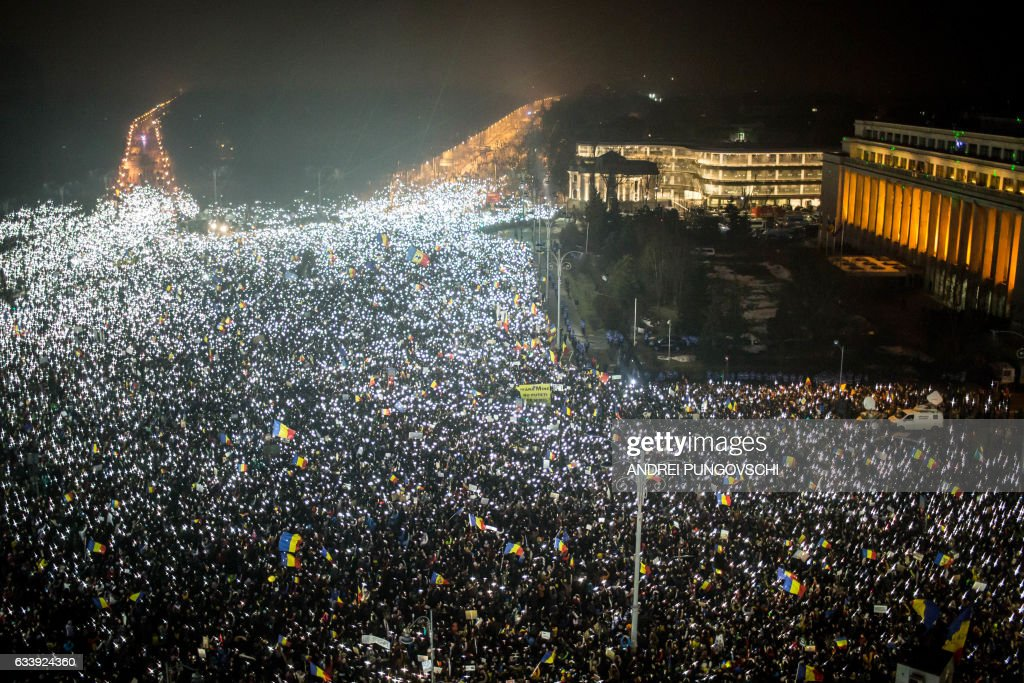 TOPSHOT - This picture shows a large view with demonstrators that turn on the lights of their mobile phones as they protest against the Romanian government's contentious corruption decree in front of the government headquarters at the Victoriei square in Bucharest on February 5, 2017. Romania's government formally repealed contentious corruption legislation that has sparked the biggest protests since the fall of dictator Nicolae Ceausescu in 1989, ministerial sources said. The emergency decree, announced on Tuesday (January 31, 2017), would have decriminalised certain corruption offences, raising concerns in Romania and outside that the government was easing up on fighting graft. Centre-right President Klaus Iohannis, elected in 2014 on an anti-graft platform, previously had called the decree 'scandalous' and moved to invoke the constitutional court. / AFP / ANDREI