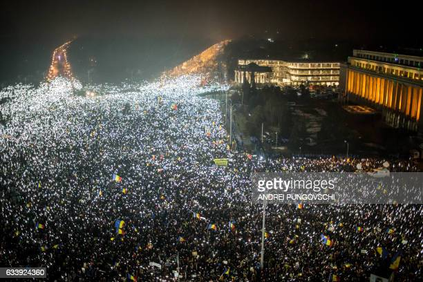 TOPSHOT This picture shows a large view with demonstrators that turn on the lights of their mobile phones as they protest against the Romanian...