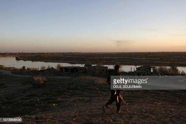 This picture shows a member of the Syrian Democratic Forces holding his rifle in Hajin in the Deir Ezzor province eastern Syria on December 15 2018...