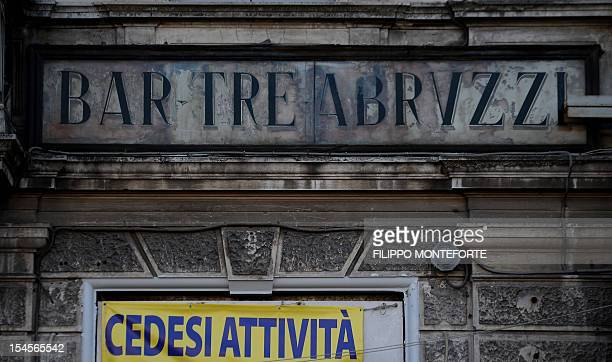 This picture shows a placard reading 'closing down' on a bar on October 22, 2012 in L'Aquila. Six Italian scientists and a government official were...