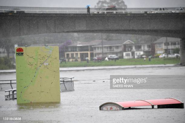 This picture shows a sign board in a flooded park along the overflowing Nepean river in Penrith suburb on March 21 as Sydney braced for its worst...