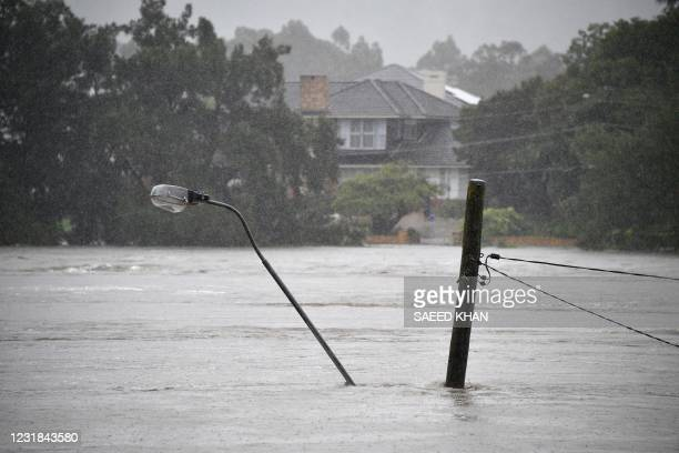 This picture shows a street light pole under floodwaters along the overflowing Nepean river in Penrith suburb on March 21 as Sydney braced for its...
