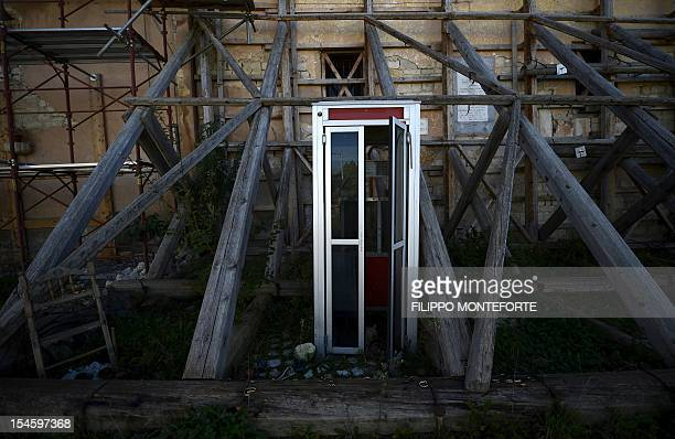 This picture shows a telephone booth near damaged buildings following the 2009 earthquake on October 22 2012 in the village of Onna Six Italian...