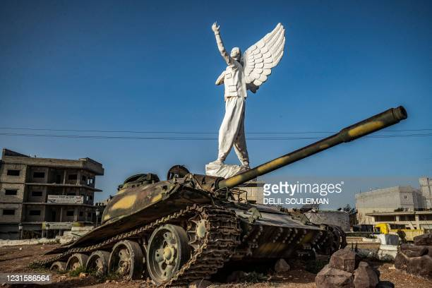 This picture shows a view of the Free Woman statue surrounded by buried tanks, in the Syrian Kurdish town of Kobane, also known as Ain al-Arab, in...