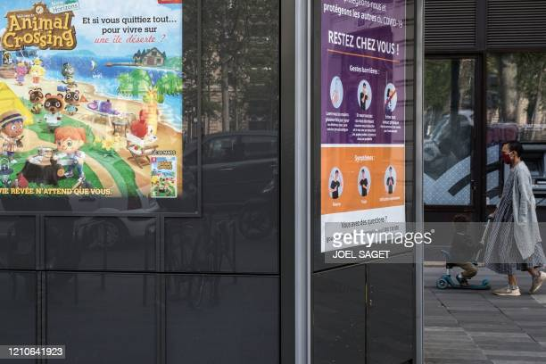"""This picture shows a woman and child walking by an advertising poster for the game """"animal crossing"""" and a information poster for the coronavirus in..."""