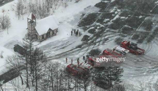 This picture shows an aerial view of ambulances and fire vehicles parked at a ski resort in the town of Kusatsu Gunma prefecture on January 23 2018...