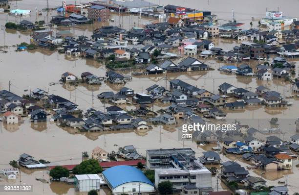 This picture shows an aerial view of flooded houses in Kurashiki Okayama prefecture on July 8 2018 Japan's Prime Minister Shinzo Abe warned on July 8...
